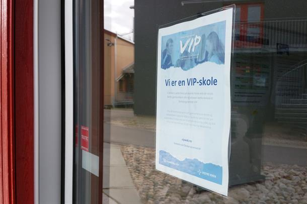 Photo of the VIP poster on a glass door. The poster reads: we are the VIP school.