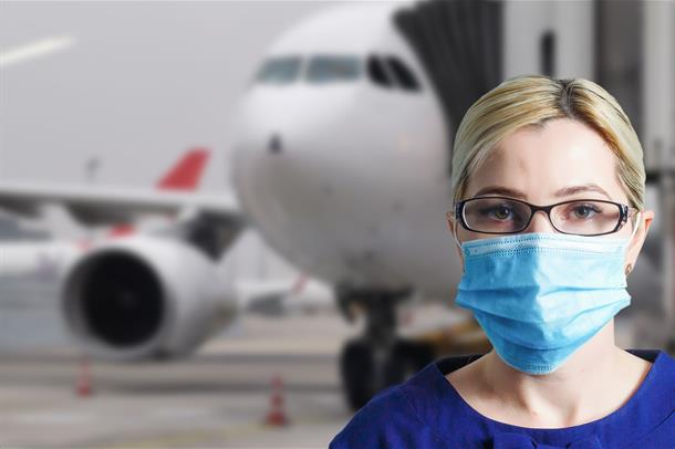 Dame med munnbind forran et fly.