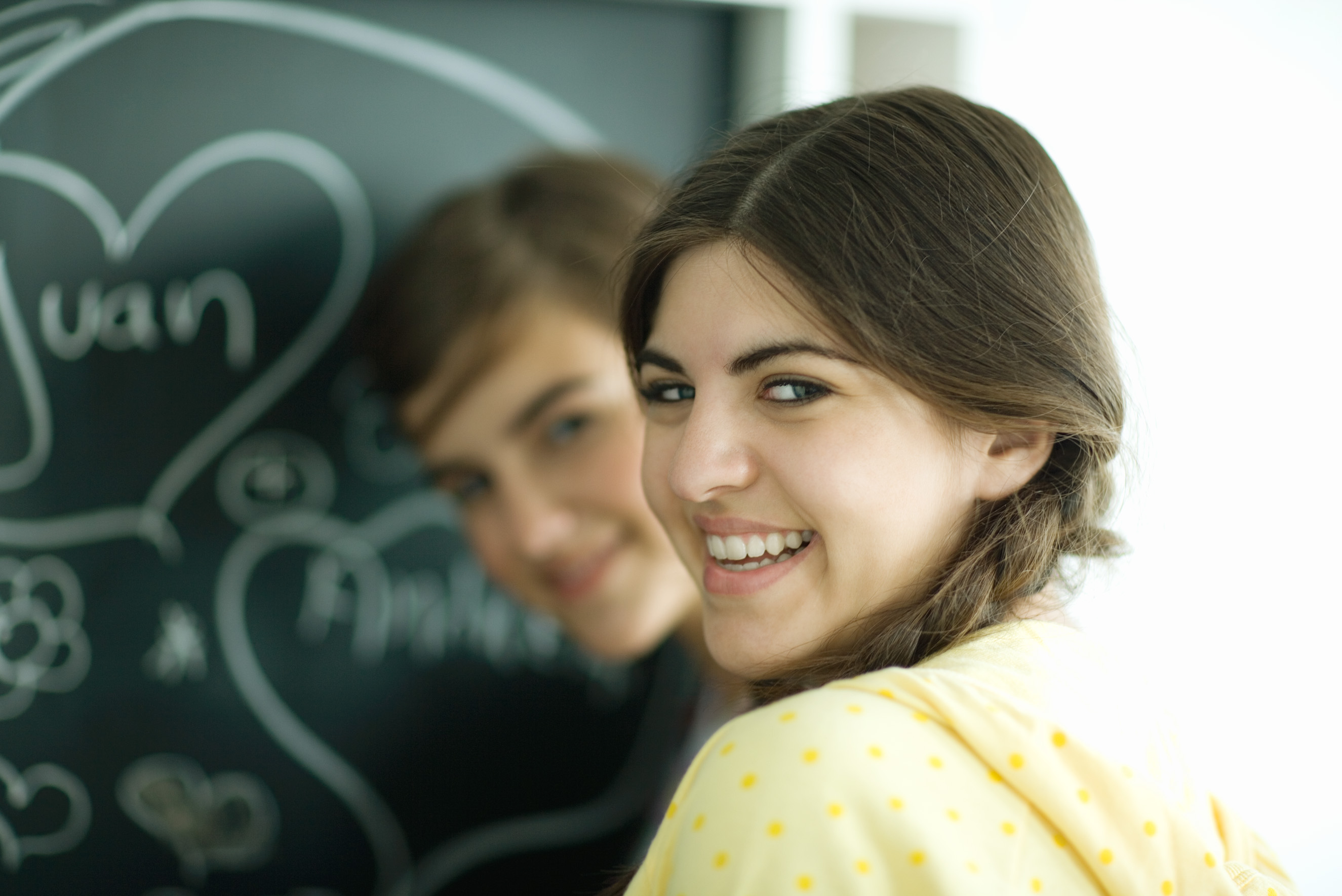 A smiling girl and a smiling boy in the background, in front of a blackboard.