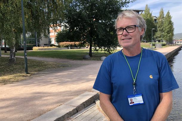 Hvit mann i 50-årene med grått kort hår står på elvebredden i Drammen med blå t-skjorte