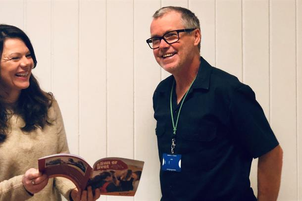 Lærum til Venstre med mørkt, langt hår holder elevheftet fra VIP i hånda og ler sammen med Hansen til venstre med briller.