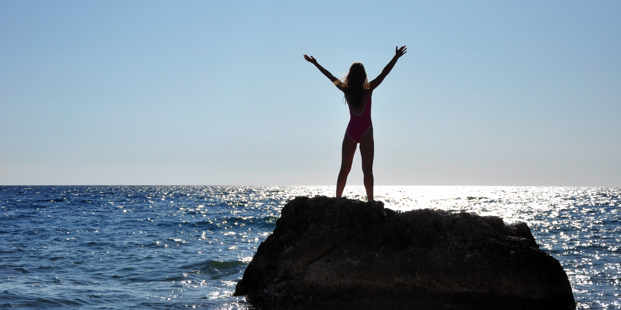A woman standing on a reef, stretching herself towards the sky.